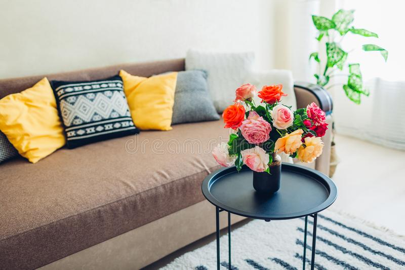 用在咖啡桌和舒适长沙发上的花装饰的客厅内部有坐垫的 新鲜的玫瑰 免版税库存图片
