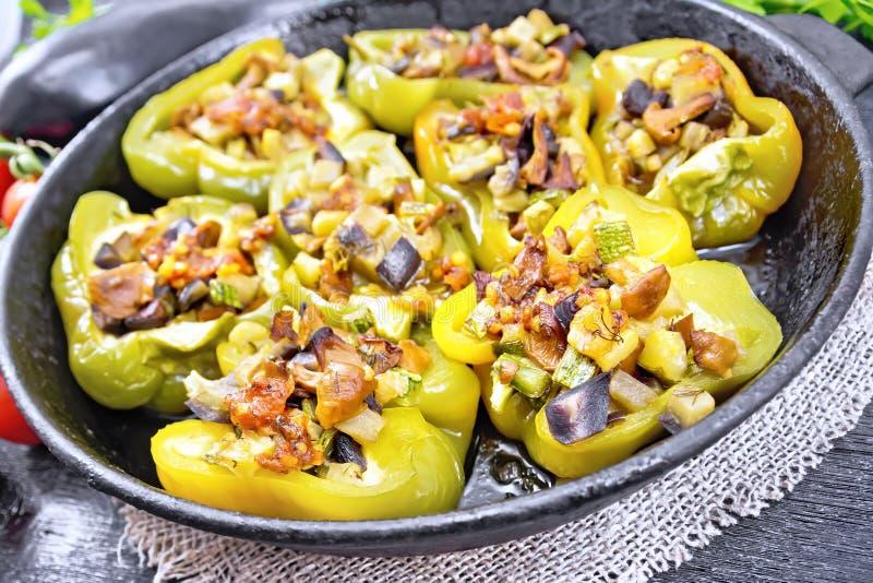 用在平底锅的菜充塞的胡椒在黑木板 免版税图库摄影