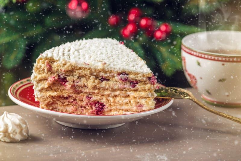 用在板材的白色奶油报道的蔓越桔蛋糕片断在圣诞树的背景 免版税库存图片