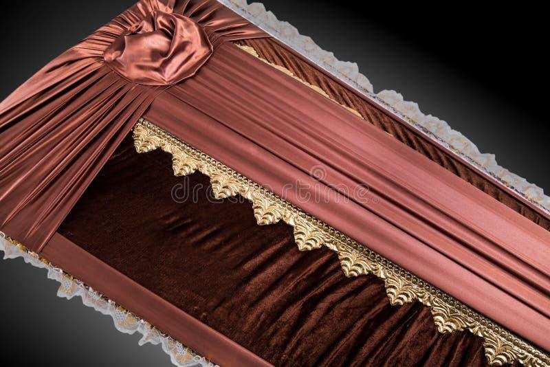 用在灰色背景的典雅的布料盖的闭合的棕色棺材 与金花的棺材特写镜头 免版税库存照片