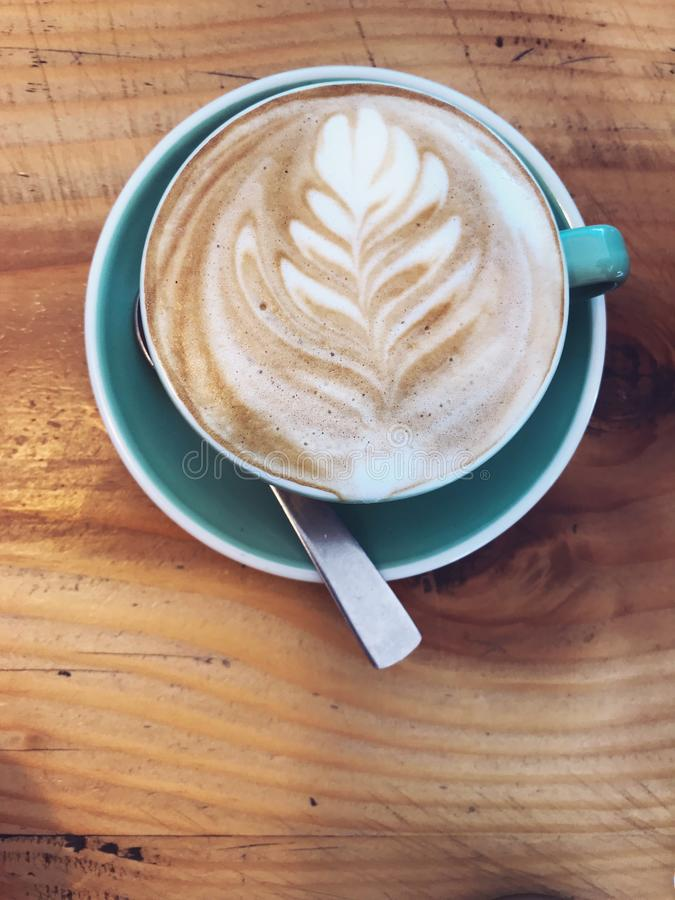 用在牛奶拿铁的树叶子装饰的热的热奶咖啡咖啡起泡沫在蓝色杯子杯子的泡沫艺术在土气木桌背景 免版税库存照片
