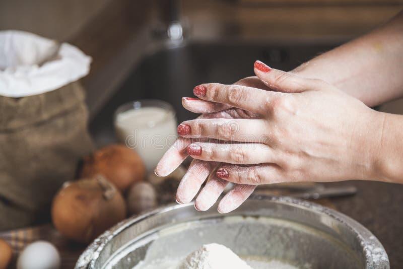 用在碗上的面粉报道的女性手 免版税图库摄影