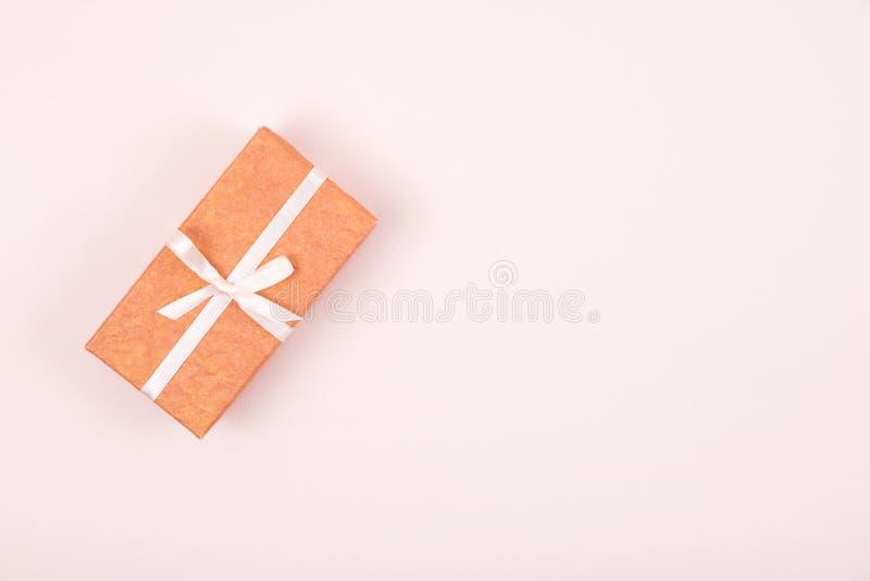 用在粉红彩笔背景的白色弓丝带装饰的简单的礼物盒 r 免版税图库摄影