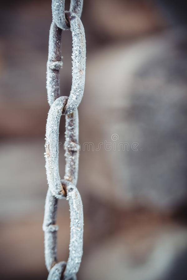 用在老木墙壁背景的白色树冰盖的金属链子 免版税库存图片