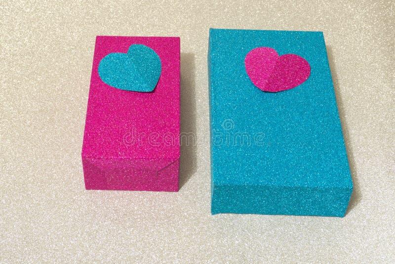用在银色发光的背景的心脏装饰的两个发光的蓝色和桃红色箱子 库存照片