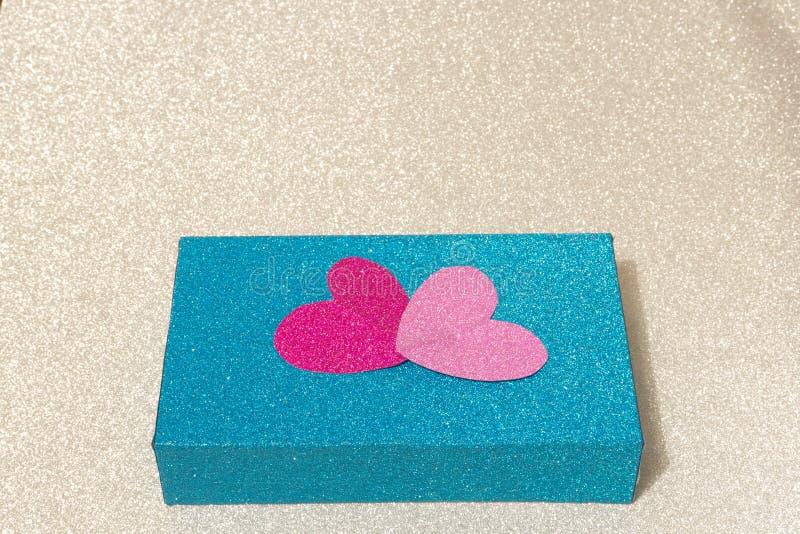 用在银色背景的心脏装饰的一个蓝色框 概念性 库存图片