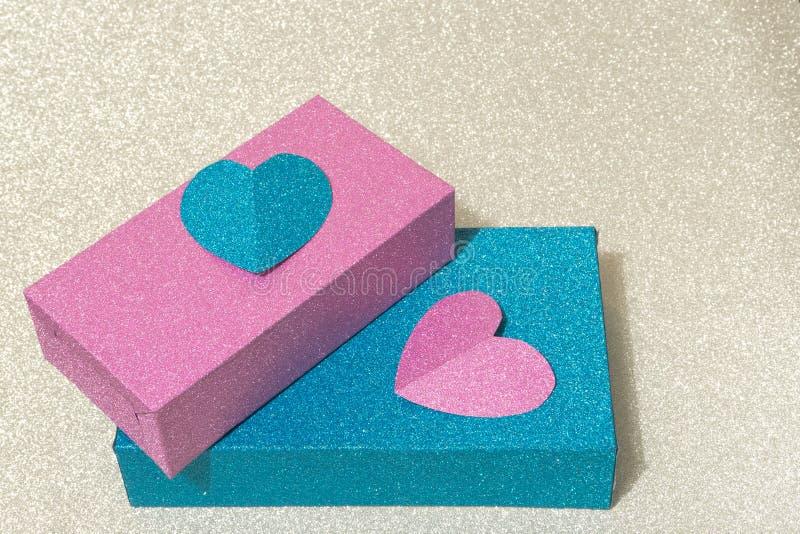 用在银色背景的心脏装饰的两个发光的蓝色和桃红色箱子 概念性 免版税库存图片