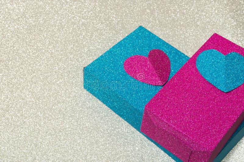 用在银色背景的心脏装饰的发光的蓝色和桃红色箱子 免版税图库摄影