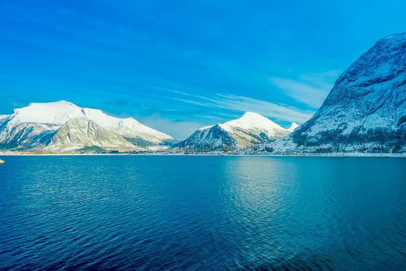用在Hurtigruten的雪报道的巨大的山沿海场面惊人的风景在蓝天的远航期间 库存图片