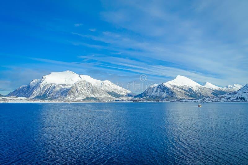 用在Hurtigruten的雪报道的巨大的山沿海场面惊人的风景在蓝天的远航期间 免版税库存图片