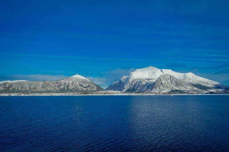 用在Hurtigruten的雪报道的巨大的山沿海场面惊人的风景在蓝天的远航期间 库存照片