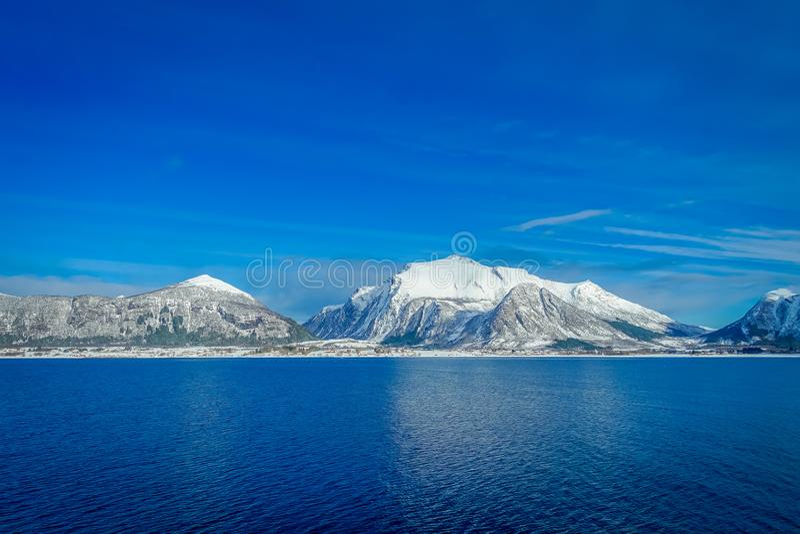 用在Hurtigruten的雪报道的巨大的山沿海场面惊人的风景在蓝天的远航期间 免版税图库摄影