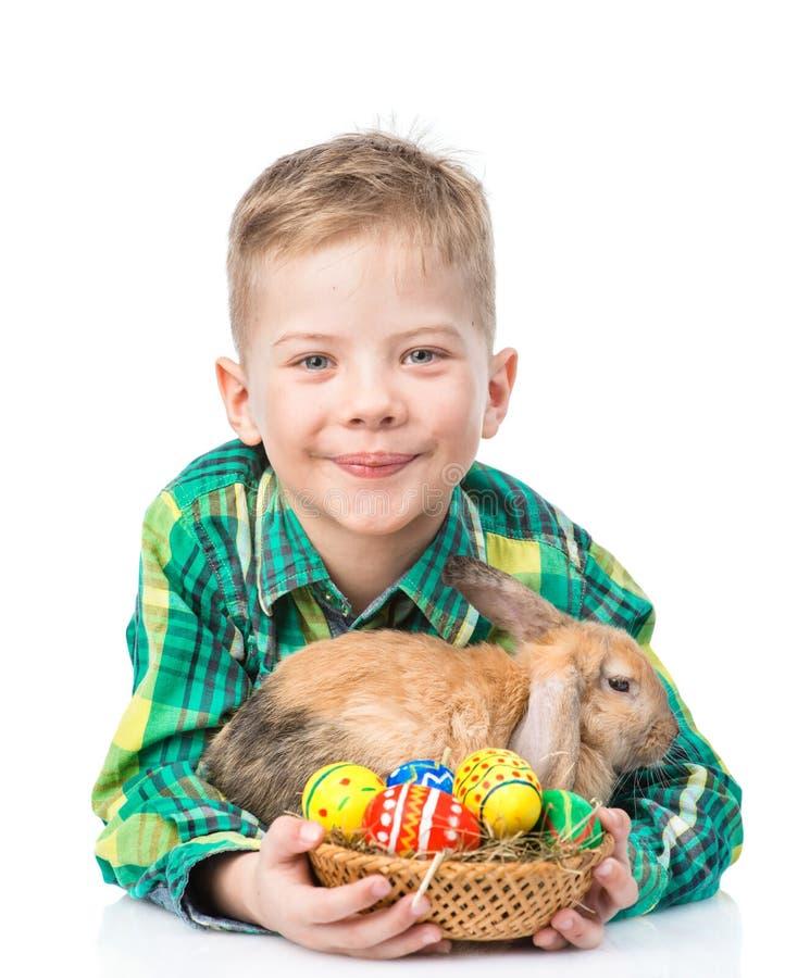 用复活节彩蛋拥抱兔子的愉快的男孩 查出在白色 库存照片