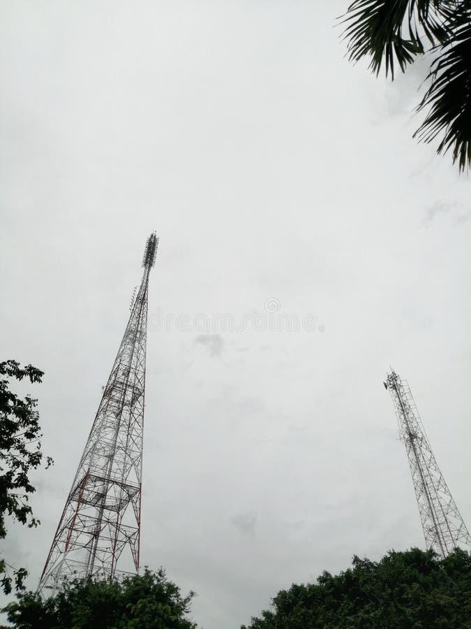 用多云天背景树木的钢框架和桁架建造的电视广播传输塔结构 免版税库存照片