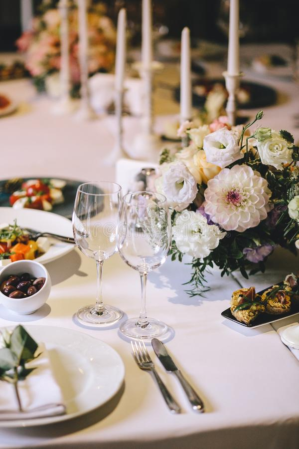 用大丽花和白色蜡烛花花束装饰的晚餐的宴会桌  在桌上,玻璃、利器和白色制地图 图库摄影
