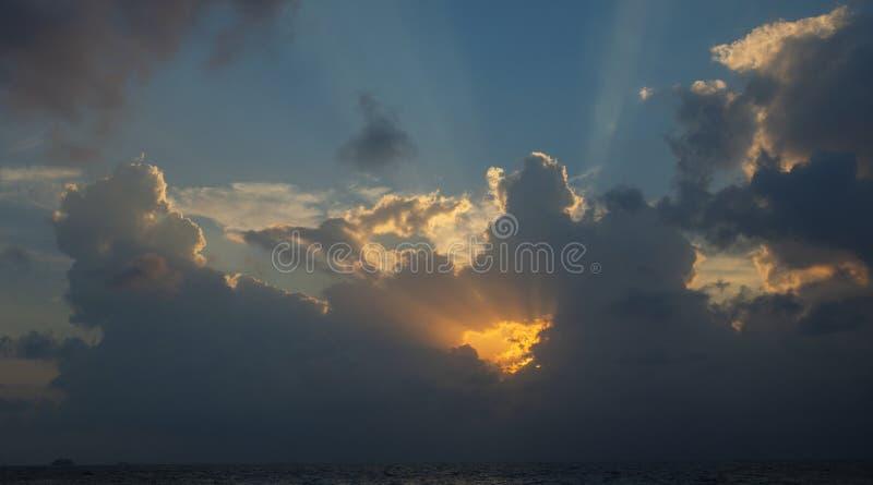 用大云彩观看天空在与黄色太阳的日落在射出光后 库存照片
