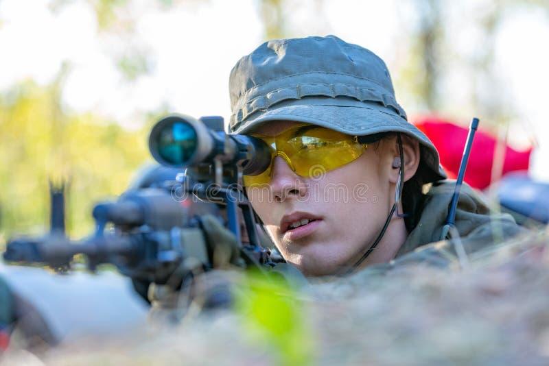 用大口径武装的狙击手,狙击步枪,在范围的射击的敌对目标从避难所,坐在埋伏 库存照片
