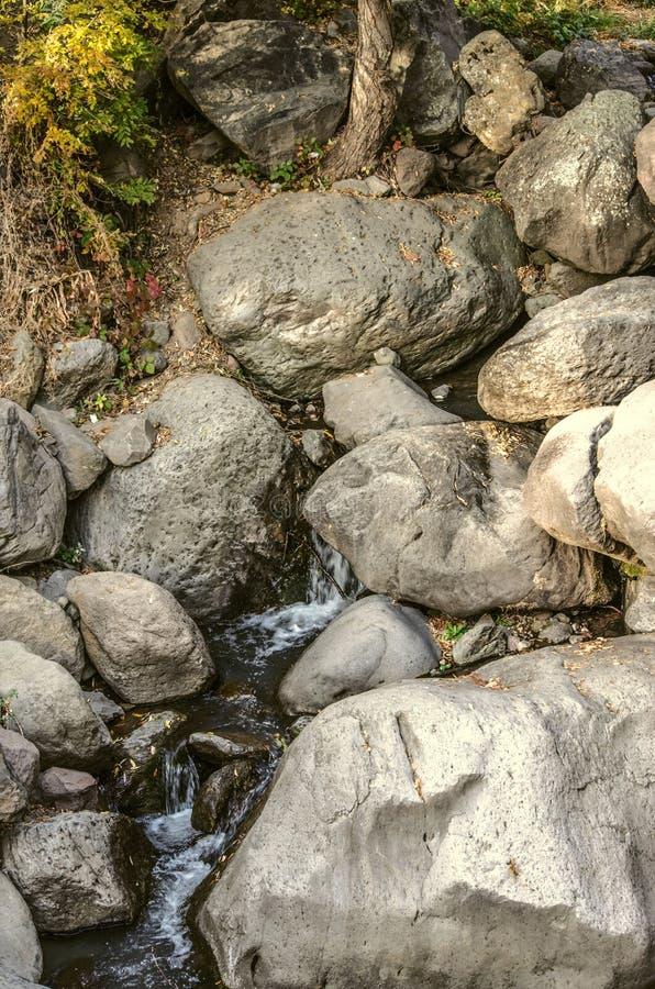 用大石头流程报道的水的水源到Gegham山的峡谷里在亚美尼亚 免版税库存图片