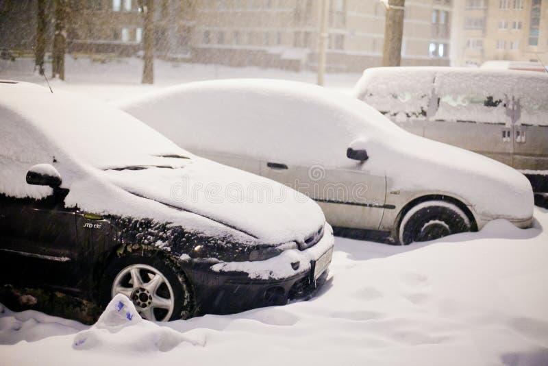 用大雪厚实的层数盖的停放的汽车在12月 免版税库存图片