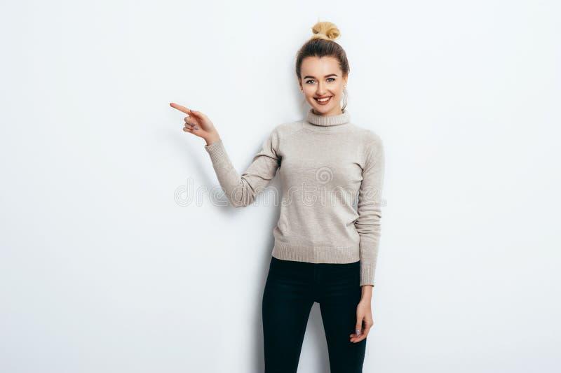 用头发小圆面包佩带在牛仔裤和毛线衣指向与在拷贝空间的食指的年轻美丽的快乐的妇女在白色墙壁 免版税图库摄影