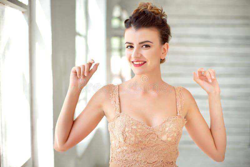 用完米黄汗衫传播的胳膊的愉快的美丽的深色头发的妇女半身画象在绝尘室 免版税库存照片