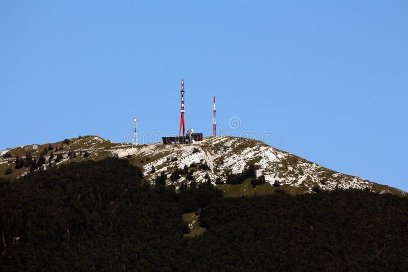 用密集的森林和岩层报道的大山上面与大厦和多个手机和电视塔 免版税库存照片
