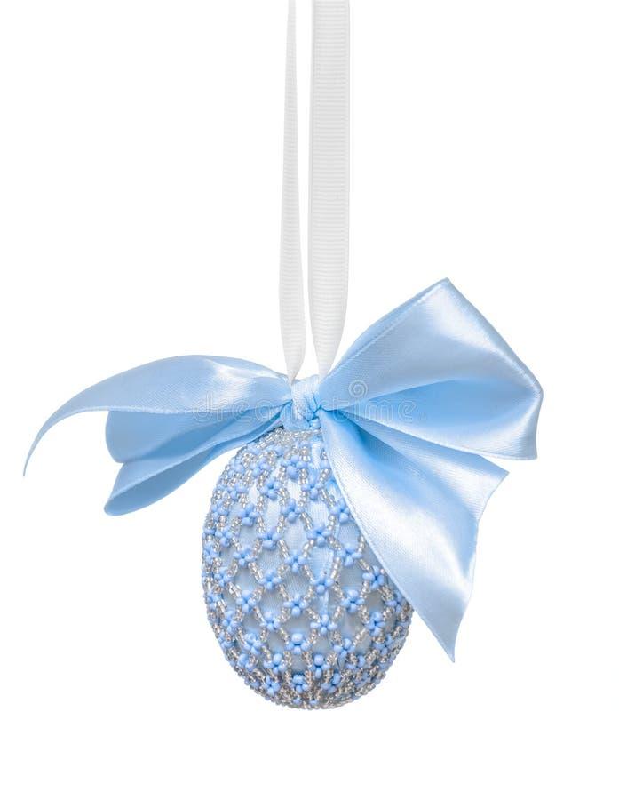 用小珠装饰的复活节彩蛋和在白色背景的一把弓 免版税库存图片
