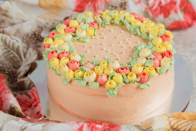 用小黄色和桃红色玫瑰装饰的奶油色蛋糕 免版税库存图片