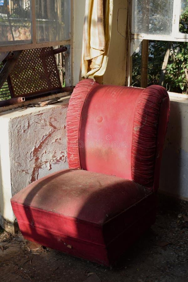 用尘土和蜘蛛网盖的葡萄酒红色扶手椅子 库存照片