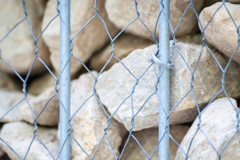 用岩石,操刀和金属条板箱做的岩石墙壁 免版税库存图片
