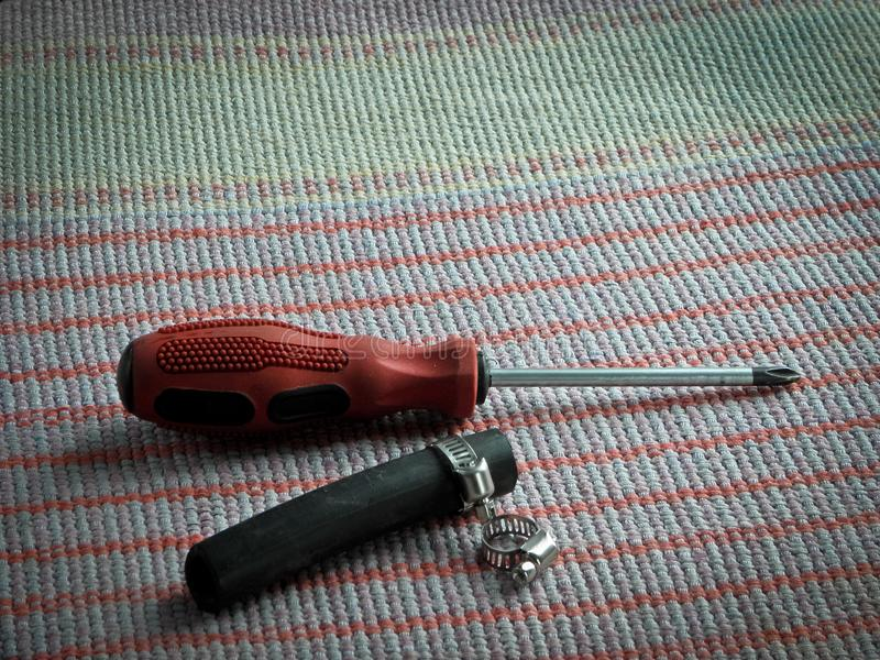 用工具加工螺丝刀,夹紧钳位和橡胶水管在桌上 库存照片