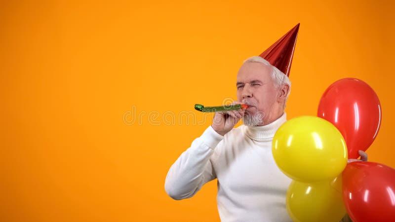 用彩色气球玩派对吹风机、活动代理的快乐高年级男人 免版税库存照片