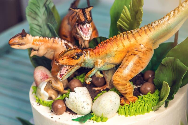 用恐龙装饰的儿童的假日白蛋糕在罗纪密林 概念孩子的想法点心 库存照片