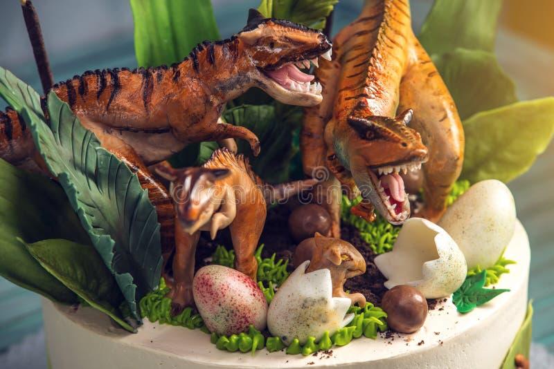 用恐龙装饰的儿童的假日白蛋糕在罗纪密林 概念孩子的想法点心 库存图片