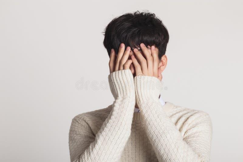 用您的手盖您的面孔,一个哀伤的亚裔年轻人的演播室画象 免版税图库摄影