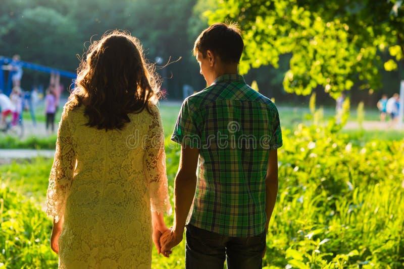 用手一起走手在公园,背面图的年轻夫妇 库存图片