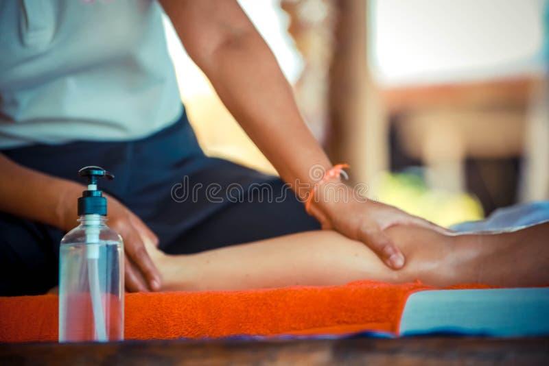 用手关闭油按摩温泉在腿在健康和健康背景的热带庭院里 库存照片