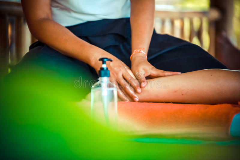 用手关闭油按摩温泉在腿在健康和健康背景的热带庭院里 免版税库存图片