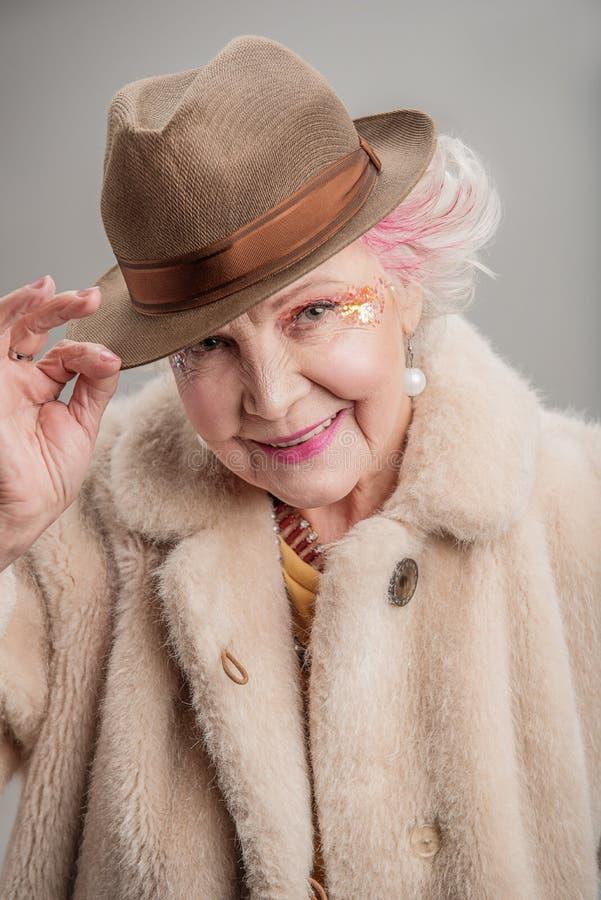 用手拿着她的帽子的正面老妇人 免版税库存照片