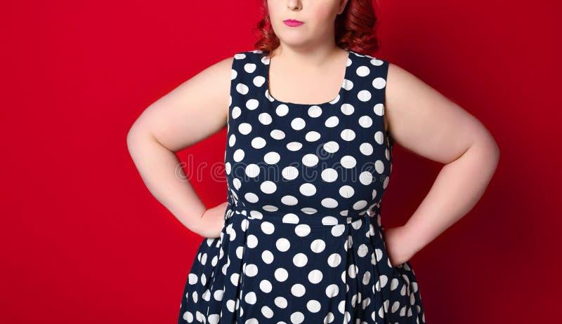 用手拿着她的面颊的一名肥胖恼怒的红头发人妇女的特写镜头 画报女孩被隔绝 库存图片
