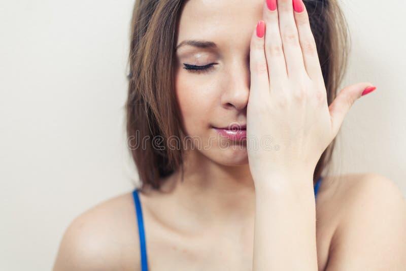 用手掩藏她的眼睛的闭合的眼睛妇女 库存照片