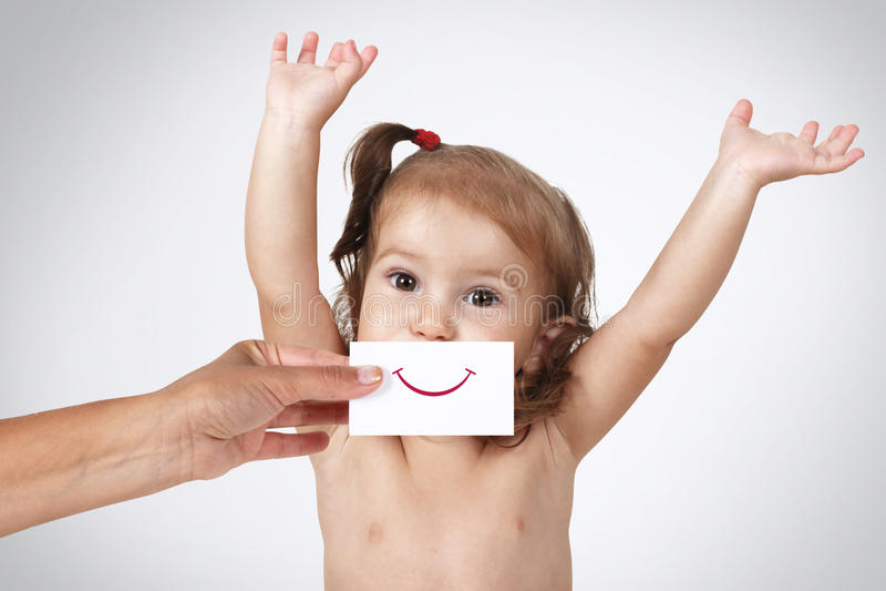 用手掩藏她的面孔的愉快的快乐的女婴与被画的微笑 免版税库存图片