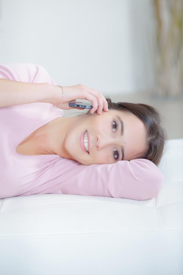 用手机躺着的女人 库存照片