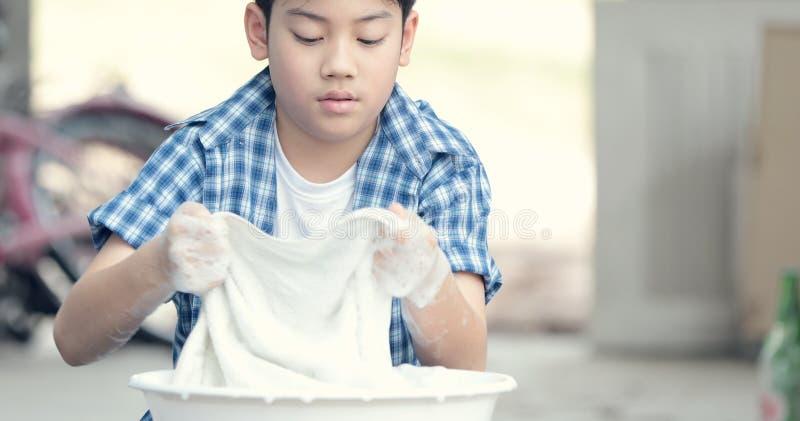 用手洗涤他的毛巾的亚裔男孩 免版税库存图片