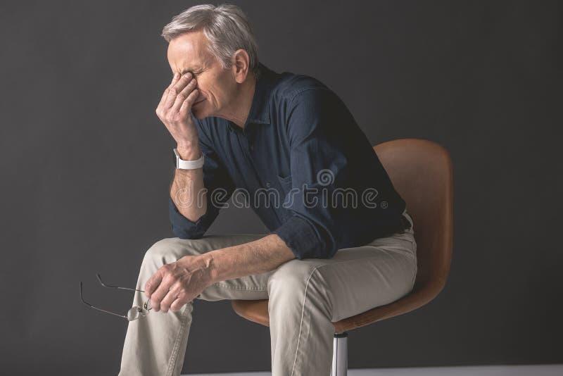 用手疲乏的老人闭合值的面孔 免版税库存照片