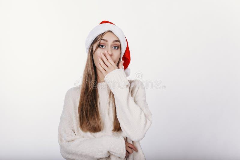 用手盖她的嘴的圣诞老人帽子的美丽的女孩 免版税库存照片