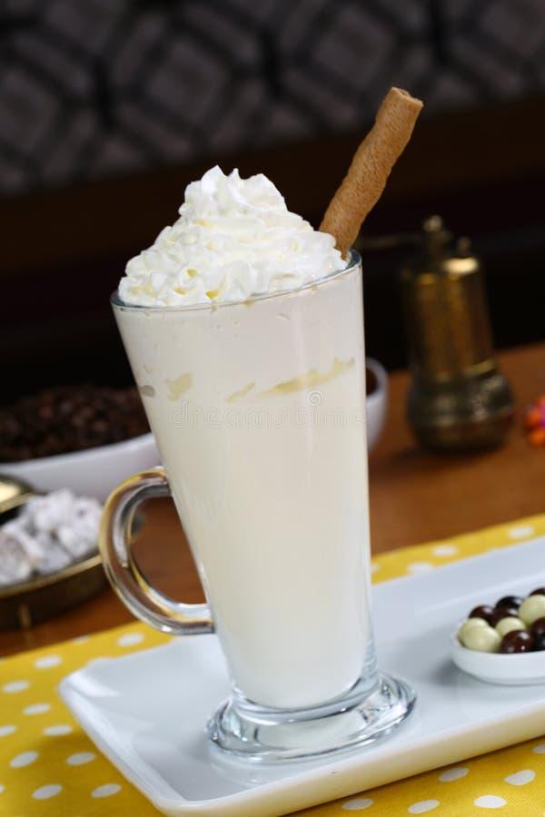 用打好的奶油装饰的热的白色巧克力 免版税库存照片