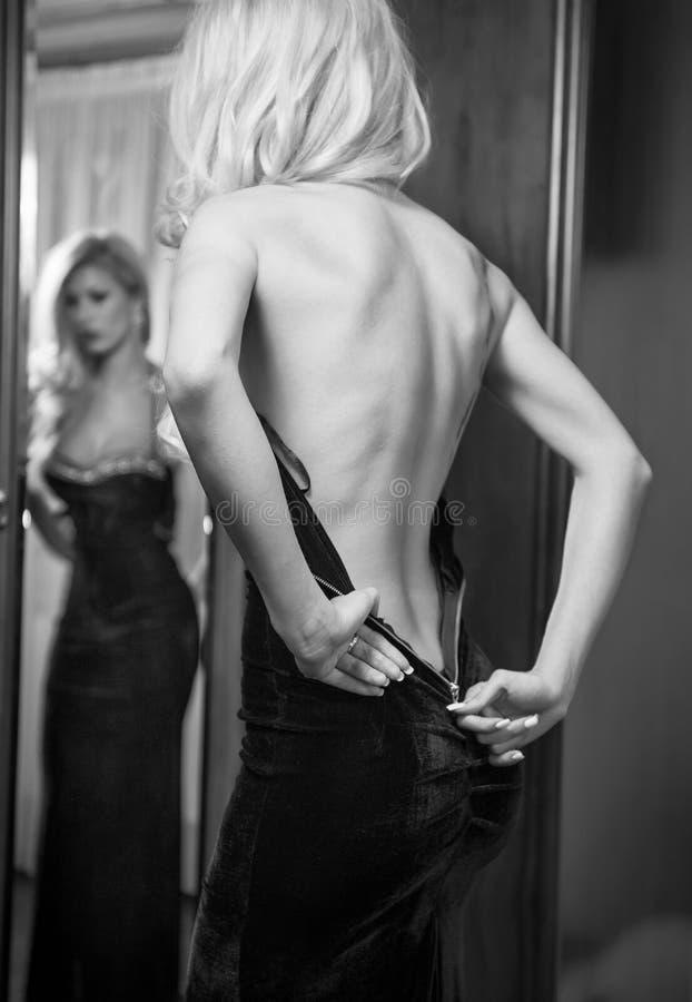用拉锁拉上她的礼服的年轻美丽的豪华妇女 免版税库存照片