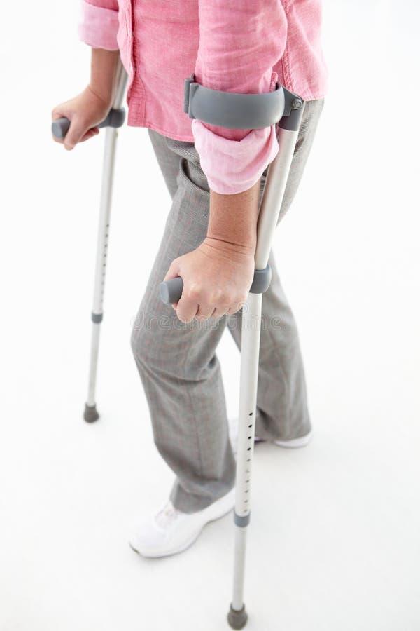 用拐杖支持走的妇女 图库摄影
