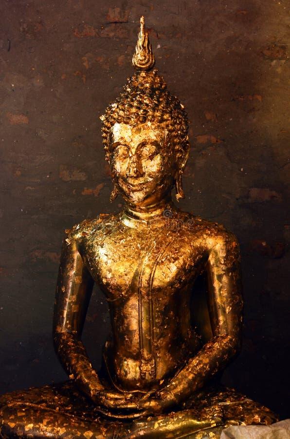 用提供盖的菩萨雕象金黄叶子wai phra在Wat亚伊柴Mongkhon寺庙在阿尤特拉利夫雷斯,泰国 库存图片